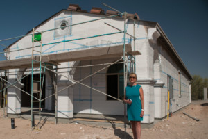 Lucy Barraza, Tucson REALTOR in front of unfinished new construction home